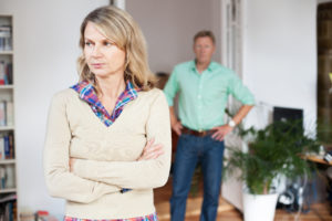 Upset woman standing with man in background at home. Mature couple having relationship difficulties.